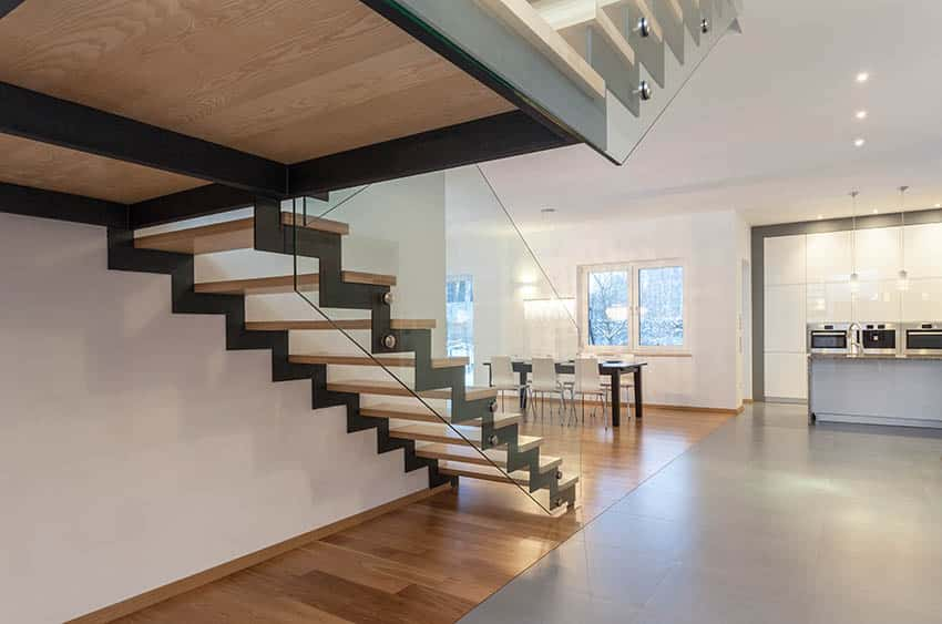 Modern floating stairs with metal supports and tempered glass side railing