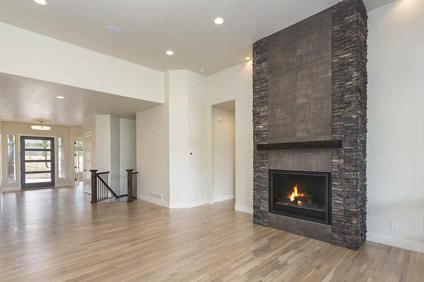 Modern granite fireplace with floating wood shelf