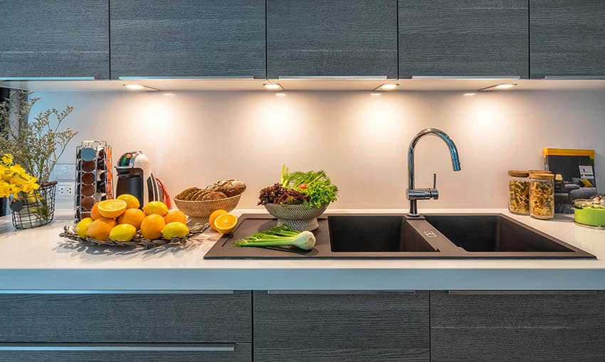 Modern kitchen with double sink, white quartz counters and dark wood veneer cabinets