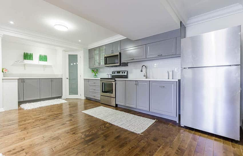 Basement kitchen with gray cabinets wood laminate floors pantry