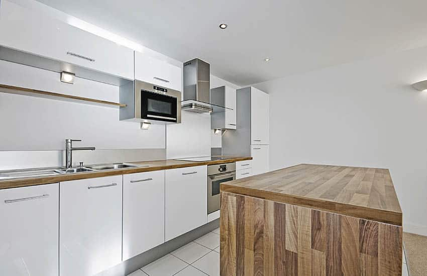 Basement kitchen with white cabinets butcher block countertops island
