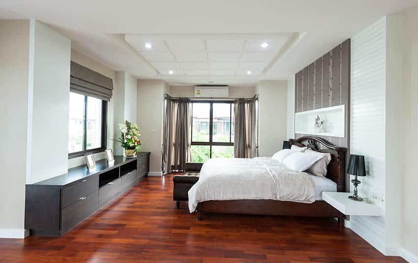 Bedroom with cherry wood floors beige and white paint