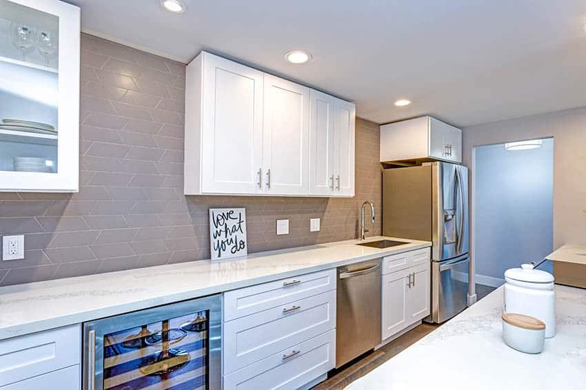 Contemporary galley style basement kitchen with shaker cabinets white quartz countertops tile backsplash