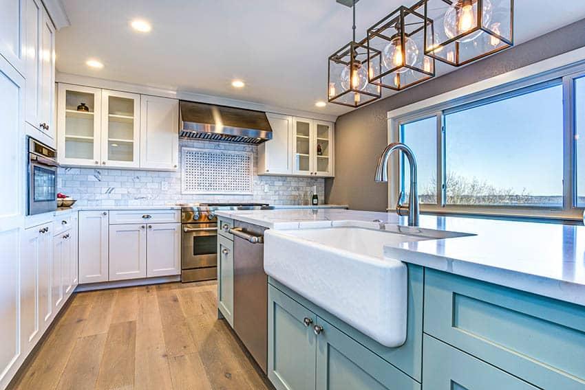 Farmhouse kitchen with apron sink in island white cabinets aqua blue island wood flooring