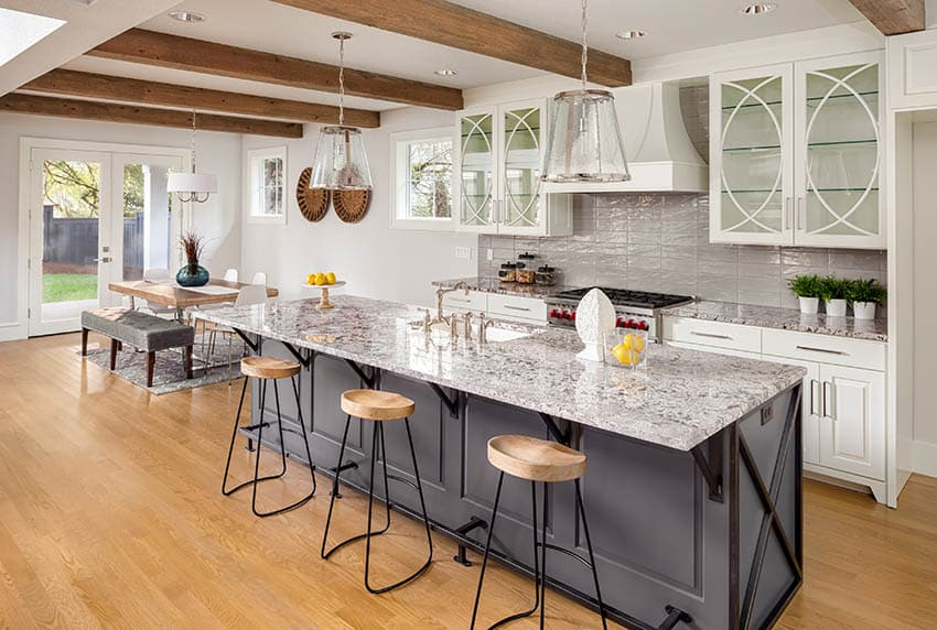 Farmhouse kitchen with light gray paint, open beam ceiling white cabinets wood flooring granite countertops