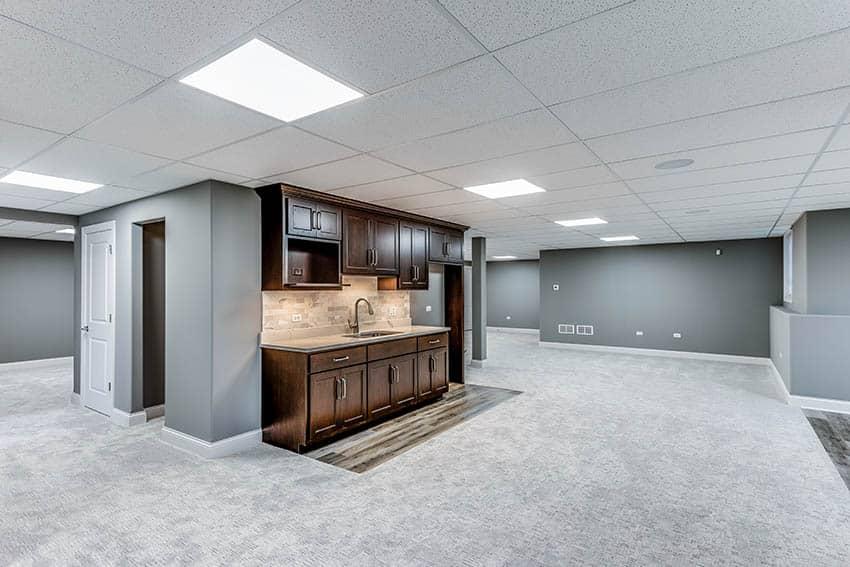 Finished basement with small kitchen with wood cabinets travertine backsplash