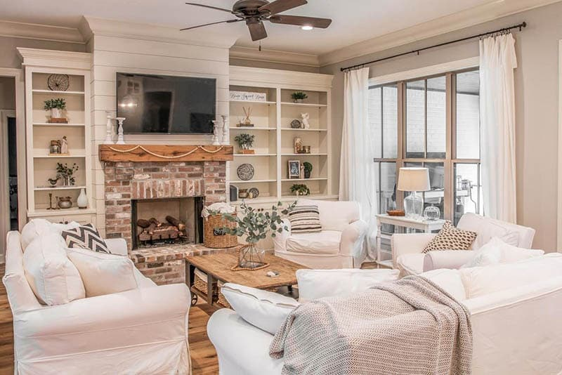 French country living room white sofas fireplace