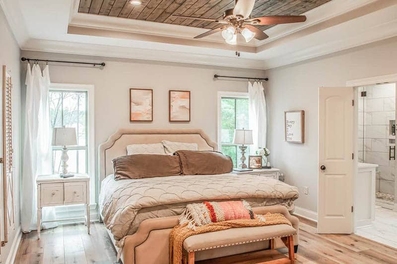 French country style bedroom with wood accent tray ceiling