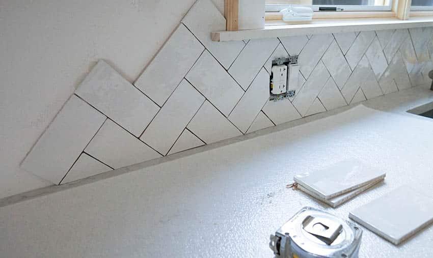 Installing herringbone tile backsplash in kitchen