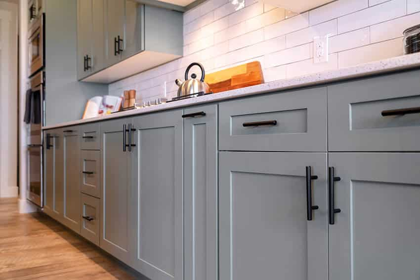 Kitchen with grey shaker cabinets black pulls white subway tile