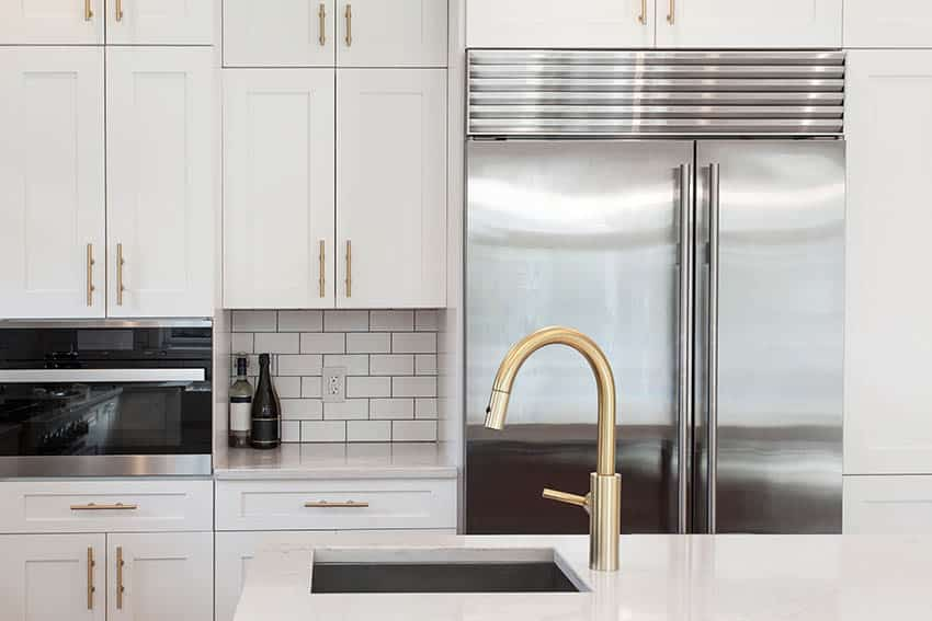Kitchen with white cabinets gold hardware pulls