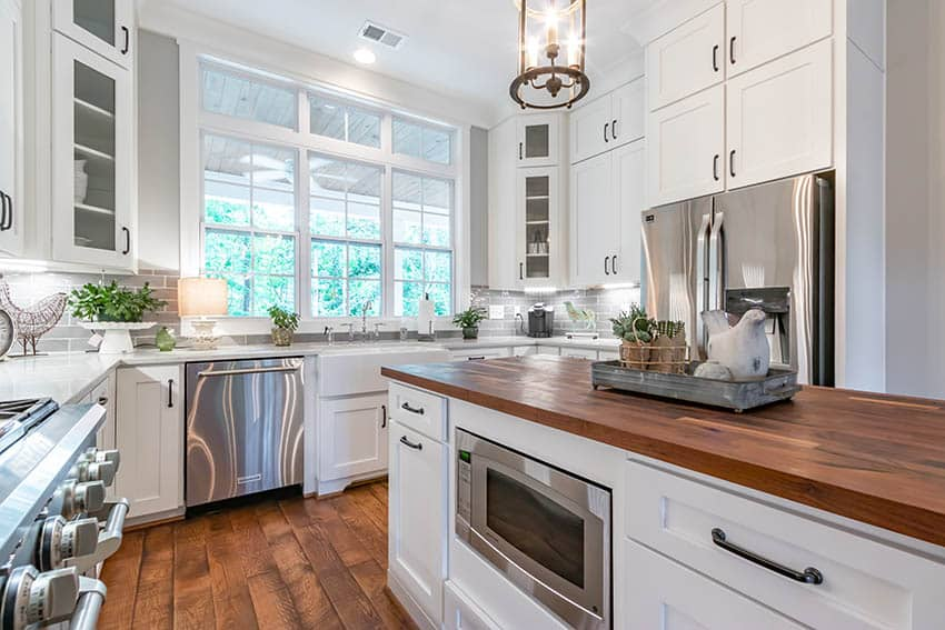 Kitchen with white cabinets hardware pulls butcher block island white quartz countertops