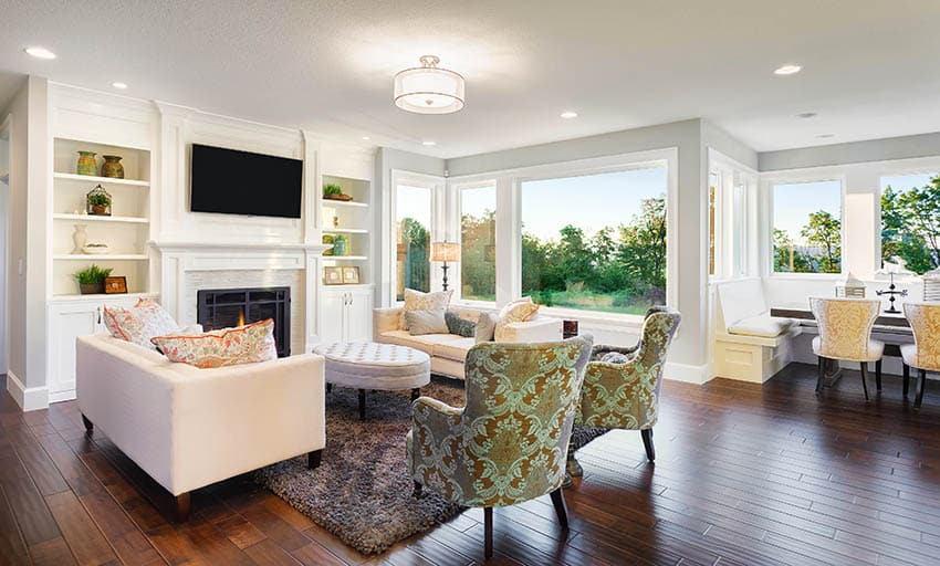 Living room with cherry wood floors light gray paint and white fireplace