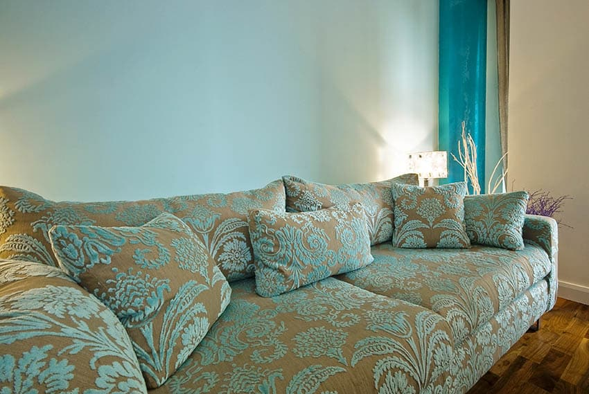 Living room with light blue paint beige accent wall and beige blue sofa