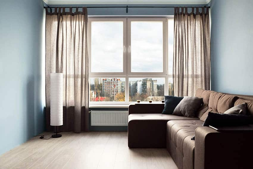 Living room with light blue paint color brown sofa and brown curtains