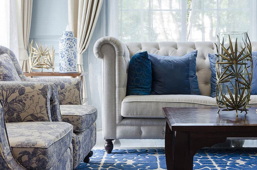 Living room with light blue wall paneling off white couch blue rug and blue white arm chairs