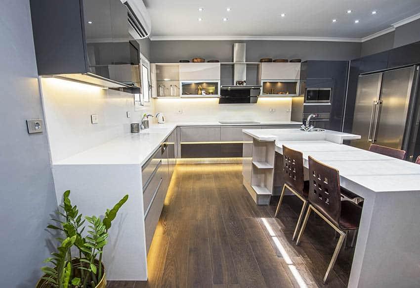 Modern basement kitchen with quartz waterfall countertop island under cabinet lighting