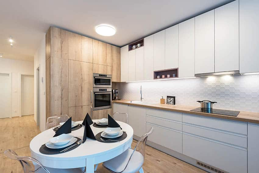 Modern basement kitchen with two tone cabinets round dining table