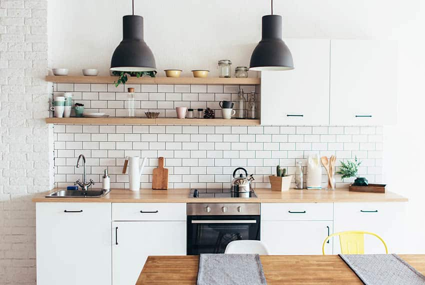 Modern farmhouse kitchen with black pendant lights wood countertop white cabinets