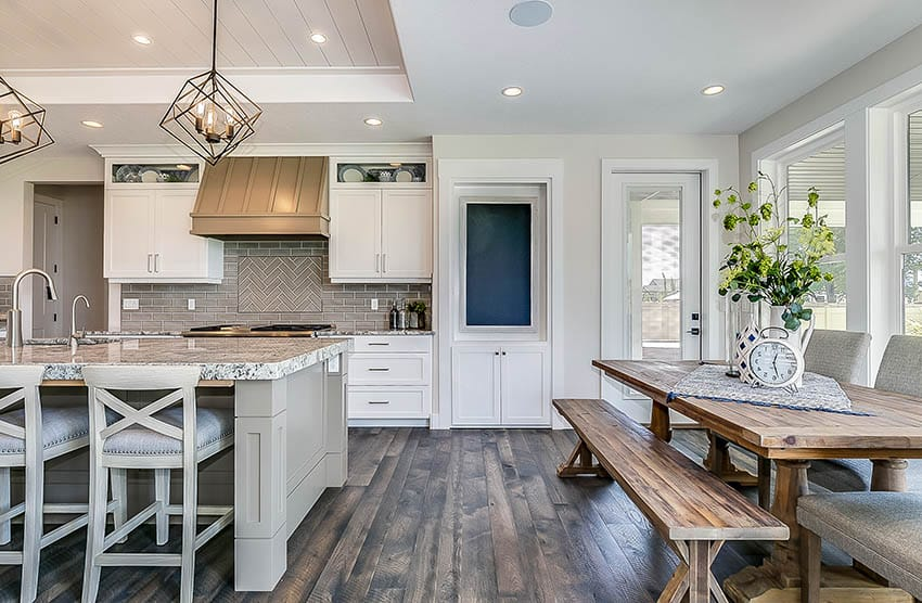 Modern farmhouse kitchen with light gray island white cabinets dark wood flooring rustic wood dining table
