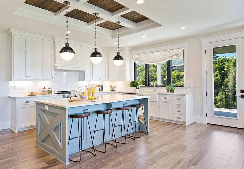 Modern farmhouse kitchen with white cabinets, blue island, white quartz counter and neutral beige wall paint