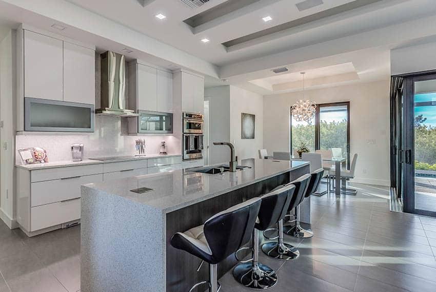 Modern kitchen with white quartz backsplash countertops wood veneer island