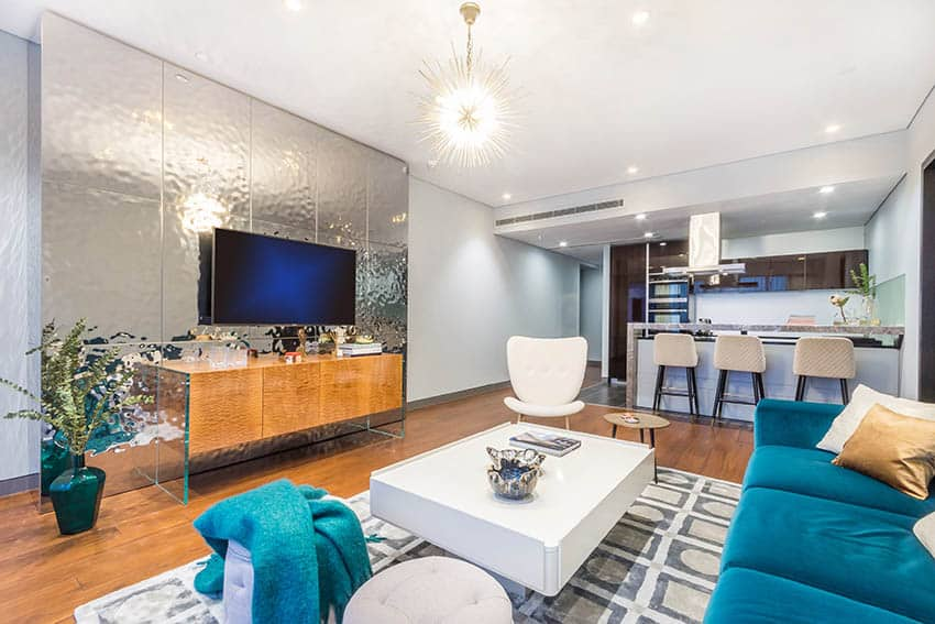Modern living room with mirror accent wall wood flooring