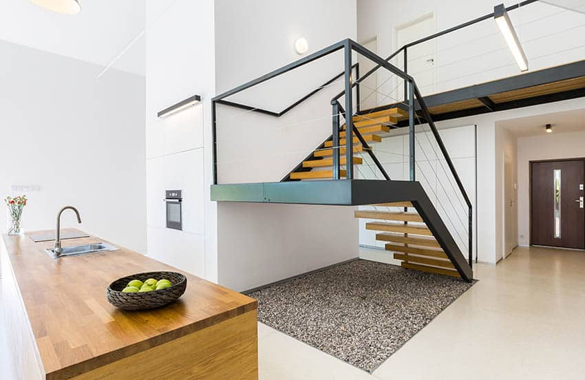 Modern switchback stairs with black hand rails wood steps in open concept entry kitchen