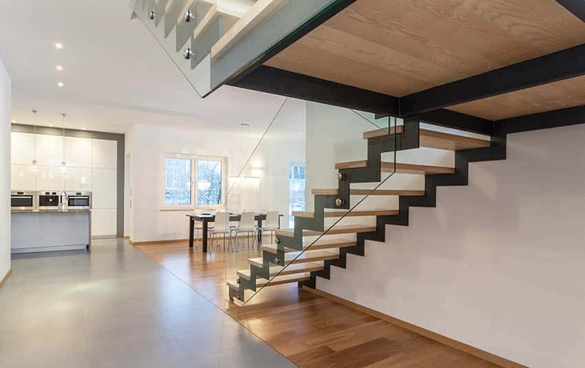 Modern u shaped stairs with metal supports and tempered glass side railing