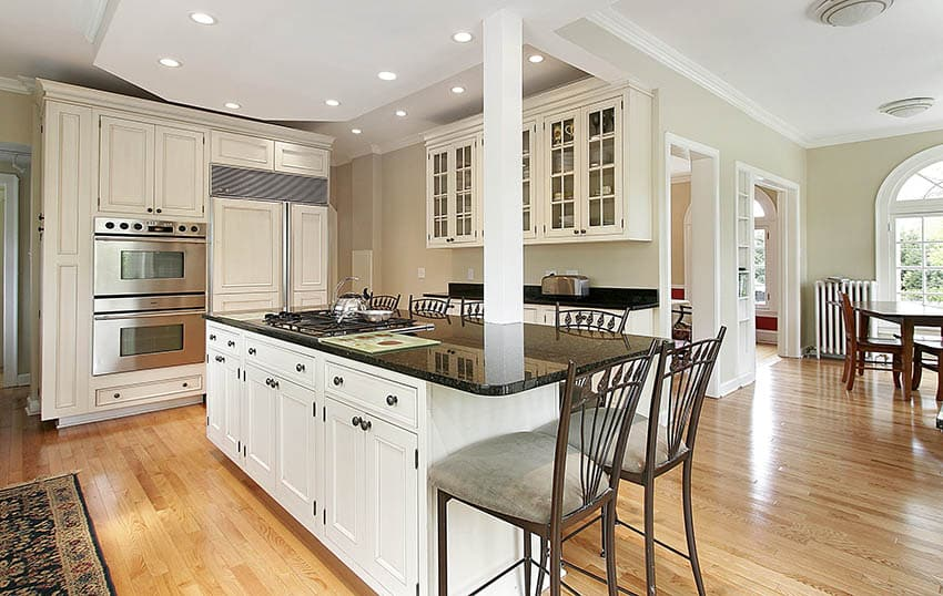 Traditional kitchen with white cabinets with knobs black granite countertops