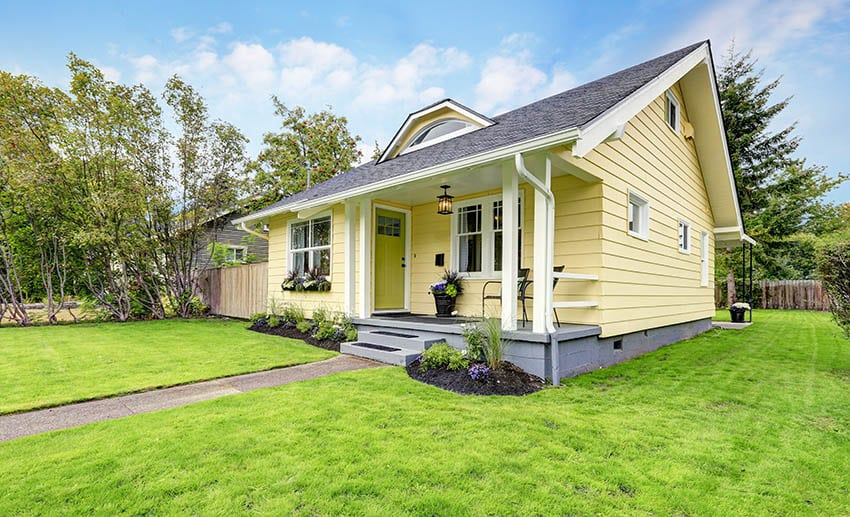 Yellow ranch style modular house with front porch