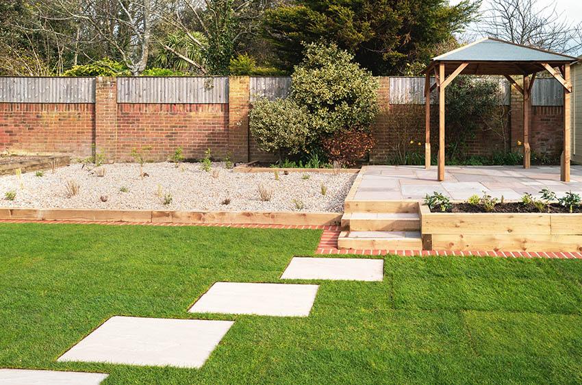 Backyard gravel landscape with pergola