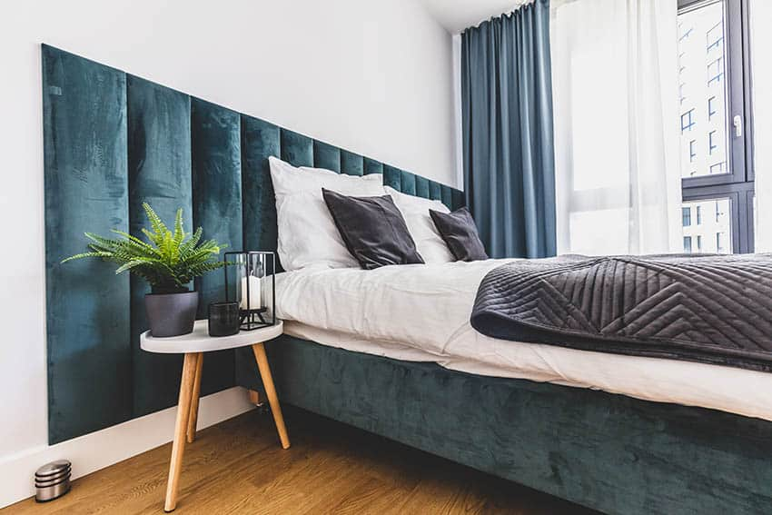 Bed with green wall mounted panel headboard