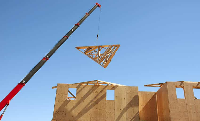 Crane lifting wooden roof truss to house