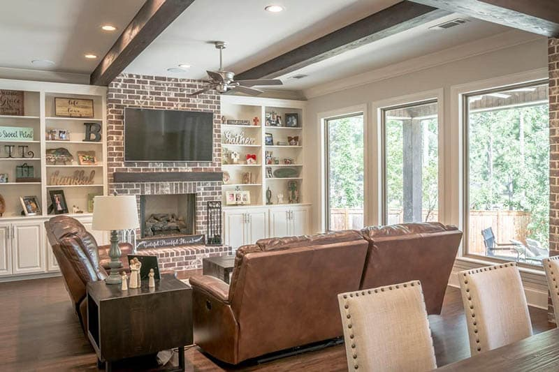 Modern farmhouse living room with brick fireplace, wood beams and wood floors
