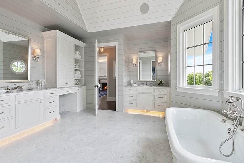 Master bathroom with picture window above tub shiplap walls white vanities