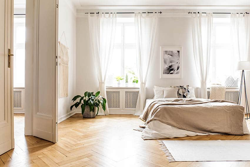 Master bedroom with white curtains wood flooring