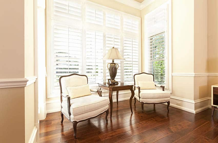 Sitting area with plantation white shutters sofa chairs wood flooring