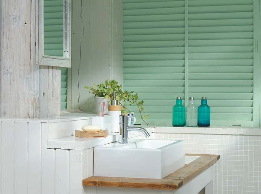Small bathroom with green plantation shutters