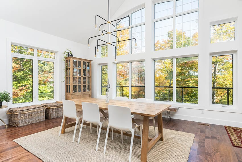 Wood craftsman dining table in room with large windows