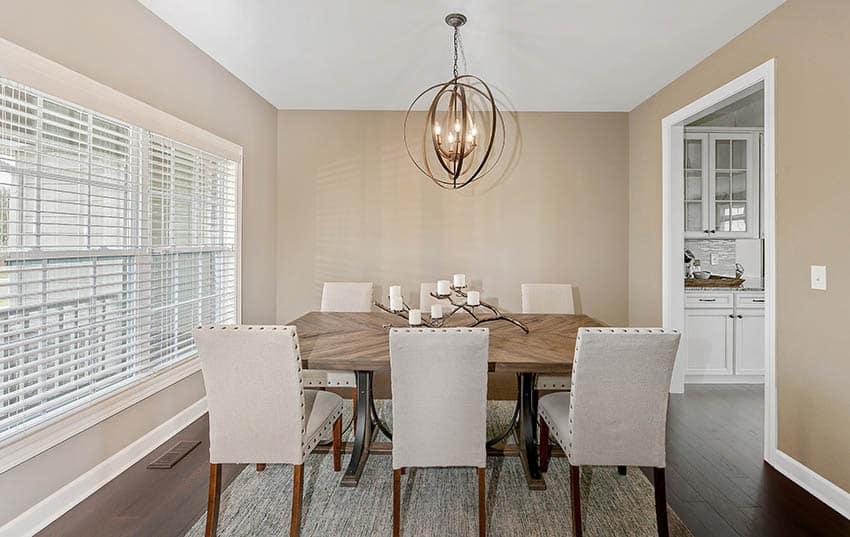 Wood dining table beige paint room globe chandelier