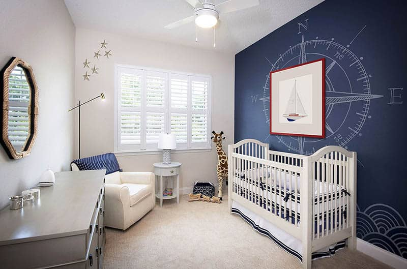 Baby nursery with crib dresser arm chair nautical accent wall