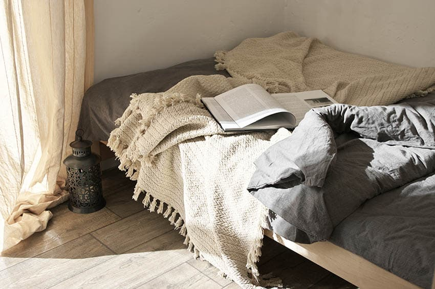 Bed with bamboo sheets woven throw blanket and book in bed