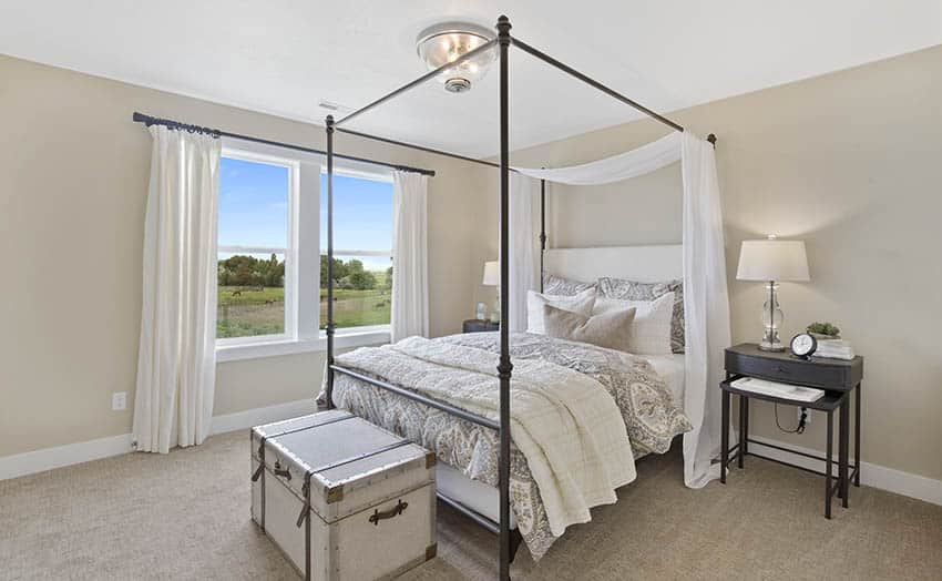 Bedroom with flush ceiling light four post bed beige wall paint white curtains