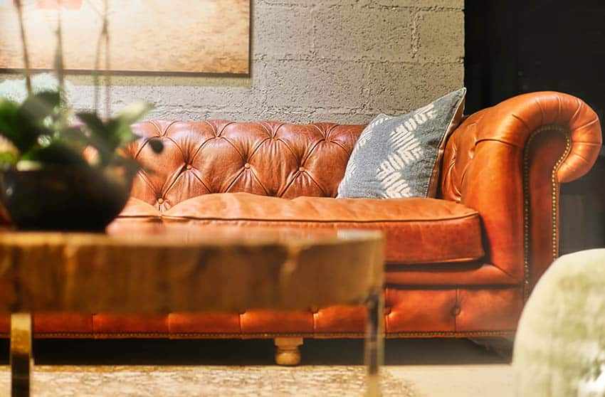 Brown leather sofa against concrete wall