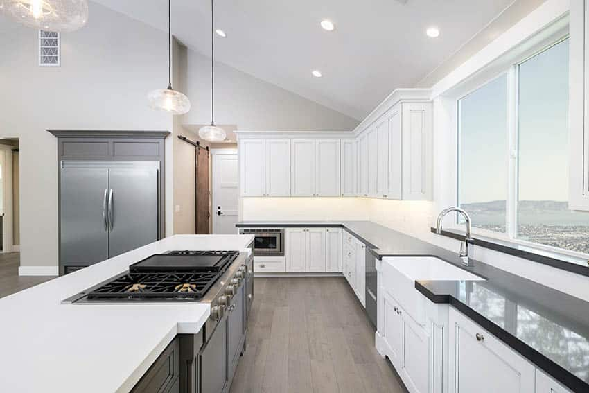 Contemporary kitchen with black and white corian countertops with black cabinet island vaulted ceiling