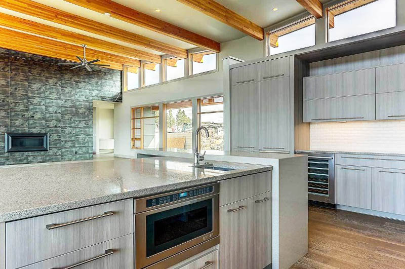 Contemporary kitchen with large island quartz waterfall countertop