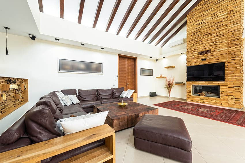 Contemporary leather sectional sofa ottoman in living room with wood coffee table mosaic fireplace