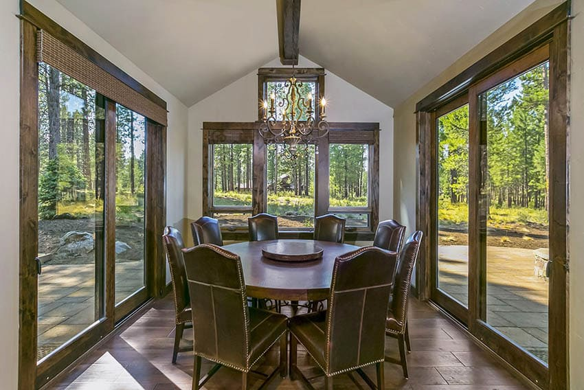 Dining room with wraparound windows round table vaulted ceiling with single beam