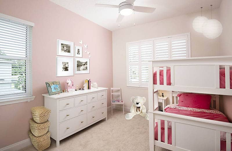 Girls bedroom with pink off white painted walls bunk beds globe pendant light